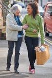 Adolescente que ayuda a la mujer mayor a Carry Shopping Fotografía de archivo