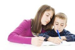 Adolescente que ayuda a su hermano con su preparación Imagen de archivo
