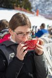 Adolescente que bebe un cuenco de bebida del chocolate caliente con crema azotada Un restaurante de la montaña colocado en una cu imagen de archivo libre de regalías