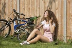 Adolescente que bebe una botella de vino Foto de archivo libre de regalías