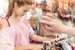 Adolescente que busca la ropa en una marca de la pulga Fotografía de archivo