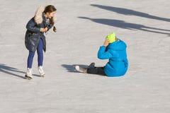 Adolescente que cae en la pista de hielo Imagen de archivo libre de regalías