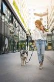 Adolescente que camina con su perro a través de la ciudad Fotos de archivo libres de regalías