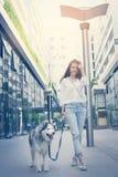 Adolescente que camina con su perro a través de la ciudad Fotos de archivo