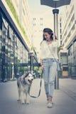 Adolescente que camina con su perro a través de la ciudad Imágenes de archivo libres de regalías