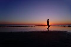 Adolescente que camina en agua en la playa en puesta del sol Foto de archivo