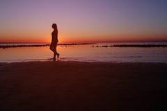 Adolescente que camina en agua en la playa en puesta del sol, Imágenes de archivo libres de regalías