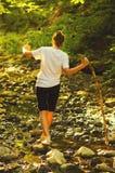 Adolescente que camina en las piedras en la corriente Imagen de archivo libre de regalías