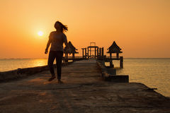 Adolescente que camina en un puente que extiende en el mar en el sunse Fotografía de archivo