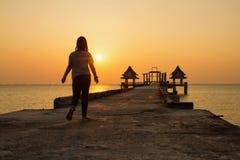 Adolescente que camina en un puente que extiende en el mar en el sunse Fotografía de archivo libre de regalías