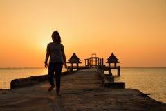 Adolescente que camina en un puente que extiende en el mar en el sunse Foto de archivo