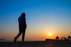Adolescente que camina en un puente que extiende en el mar en el sunse Fotos de archivo