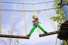 Adolescente que camina en un tablero en un parque de la cuerda Imagen de archivo libre de regalías