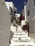 Adolescente que camina la calle estrecha de Mykonos Fotos de archivo