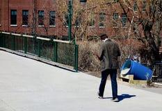 Adolescente que camina mientras que lee o manda un SMS Foto de archivo libre de regalías