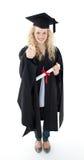 Adolescente que celebra la graduación con los pulgares para arriba Imagenes de archivo