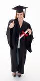 Adolescente que celebra la graduación con los pulgares para arriba Foto de archivo libre de regalías