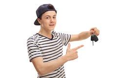 Adolescente que celebra una llave y señalar del coche Foto de archivo libre de regalías