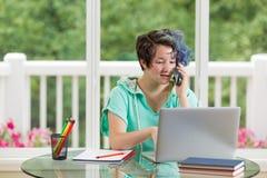 Adolescente que charla en el teléfono mientras que trabaja en sus estudios en h Imagen de archivo libre de regalías