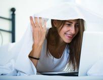 Adolescente que charla en línea cubierto con la manta Foto de archivo