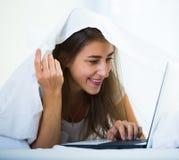 Adolescente que charla en línea cubierto con la manta Imágenes de archivo libres de regalías