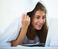 Adolescente que charla en línea cubierto con la manta Fotografía de archivo libre de regalías