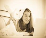 Adolescente que charla en línea cubierto con la manta Imagen de archivo libre de regalías