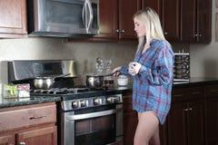 Adolescente que cocina llevando solamente un top Imagen de archivo libre de regalías