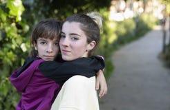 Adolescente que coge a su pequeña hermana en el jardín de una casa Fotos de archivo libres de regalías