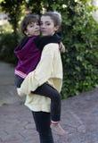 Adolescente que coge a su pequeña hermana en el jardín de una casa Foto de archivo