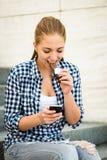 Adolescente que come el chcolate que mira en teléfono Fotos de archivo libres de regalías
