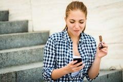 Adolescente que come el chcolate que mira en teléfono Foto de archivo libre de regalías