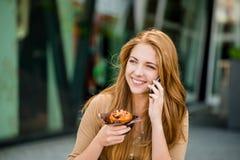 Adolescente que come el mollete que mira en teléfono Imagen de archivo libre de regalías