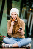 Adolescente que come el mollete que mira en teléfono Fotografía de archivo