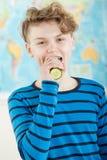 Adolescente que come el pepino entero delante del mapa Foto de archivo libre de regalías