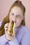 Adolescente que come el perrito caliente Foto de archivo