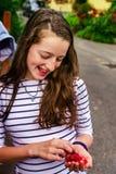 Adolescente que come la frambuesa en el jardín Foto de archivo libre de regalías