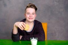 Adolescente que come la galleta y la leche de la bebida Imagen de archivo libre de regalías