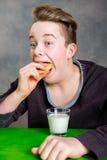 Adolescente que come la galleta y la leche grabby de la bebida Foto de archivo