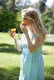 Adolescente que come la naranja amarga Imagenes de archivo