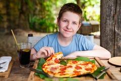 Adolescente que come la pizza Imagenes de archivo