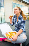 Adolescente que come la pizza en calle Fotografía de archivo libre de regalías