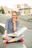 Adolescente que come la pizza en calle Foto de archivo