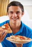 Adolescente que come la pizza en casa Imágenes de archivo libres de regalías