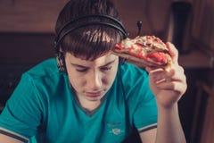 Adolescente que come la pizza que se sienta en un ordenador portátil Imágenes de archivo libres de regalías