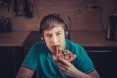 Adolescente que come la pizza que se sienta en un ordenador portátil Imagen de archivo libre de regalías