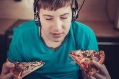 Adolescente que come la pizza que se sienta en un ordenador portátil Foto de archivo libre de regalías