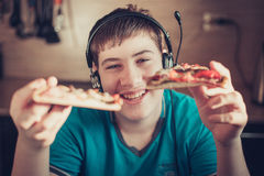 Adolescente que come la pizza que se sienta en un ordenador portátil Imagen de archivo