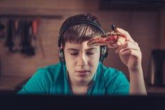 Adolescente que come la pizza que se sienta en un ordenador portátil Foto de archivo