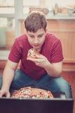 Adolescente que come la pizza que se sienta en un ordenador portátil Imagenes de archivo